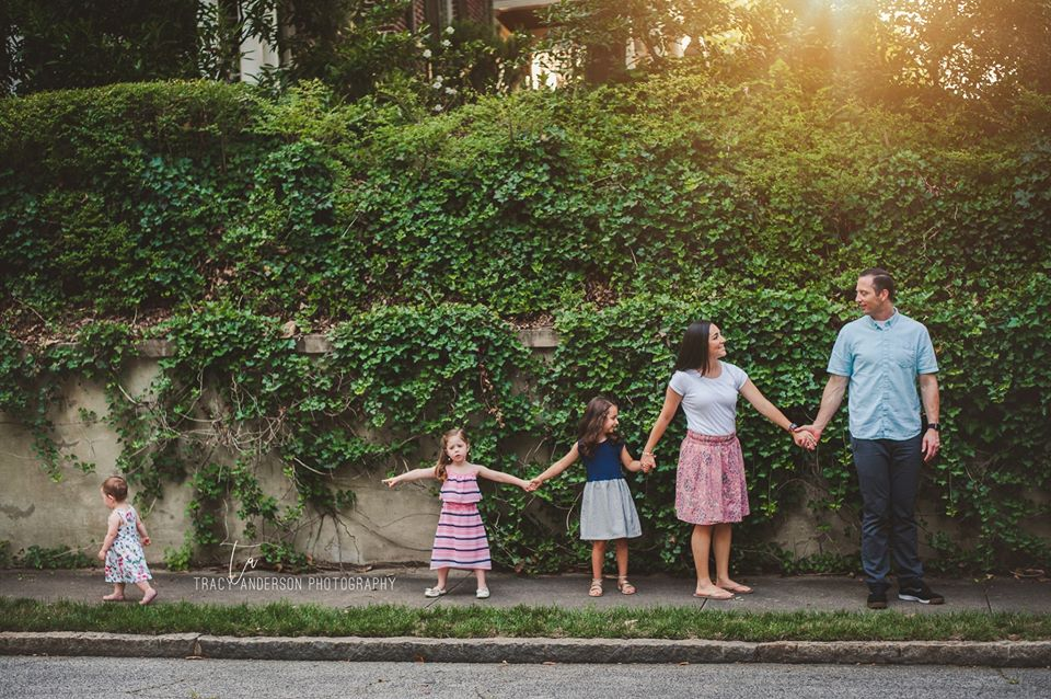 portrait of family holding hands in front of vine covered wall