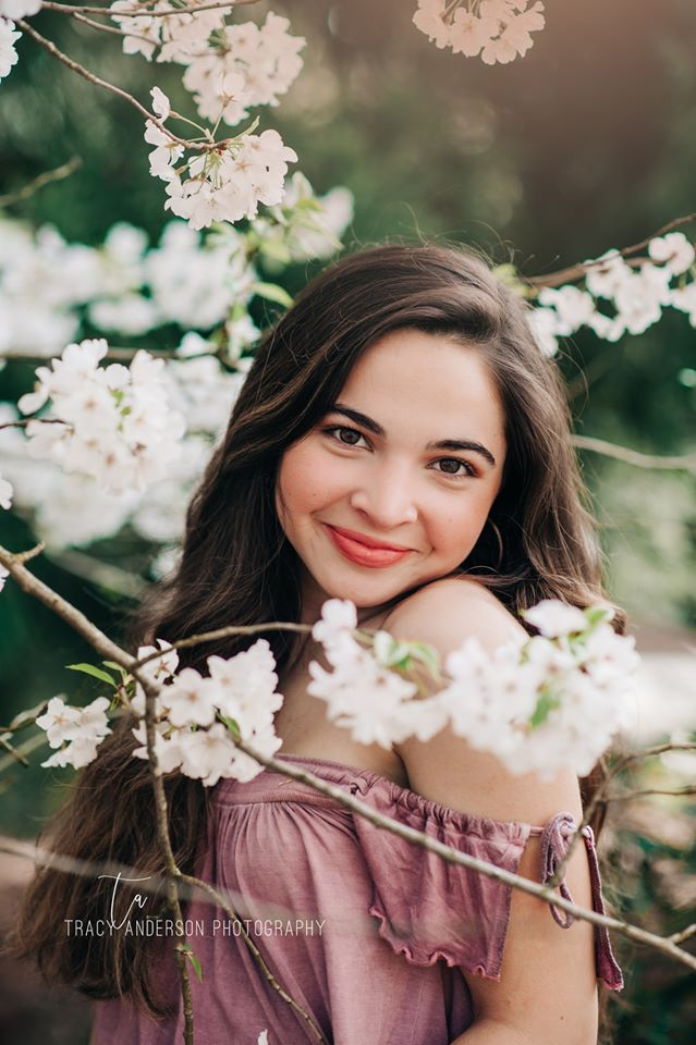 portrait of a girl posed near a tree with white flowers