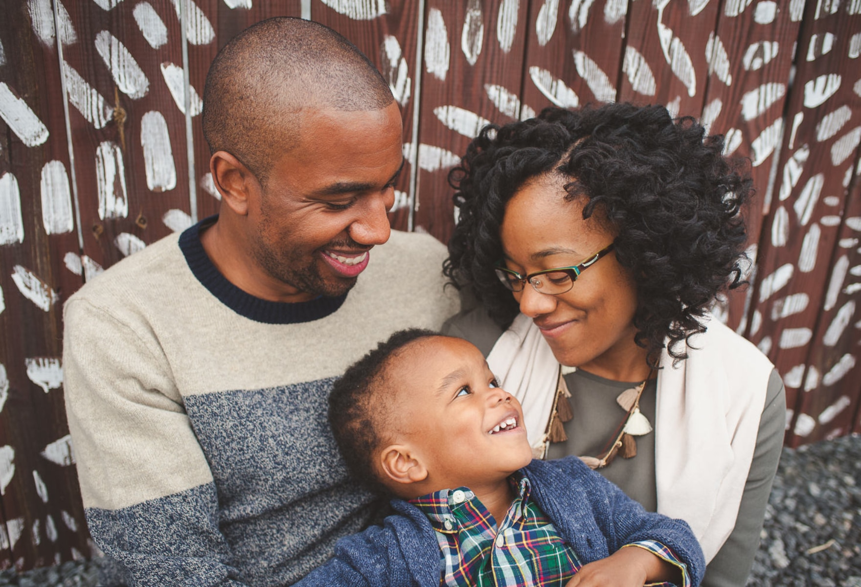 portrait of black family of 3 sitting together and smiling at each other