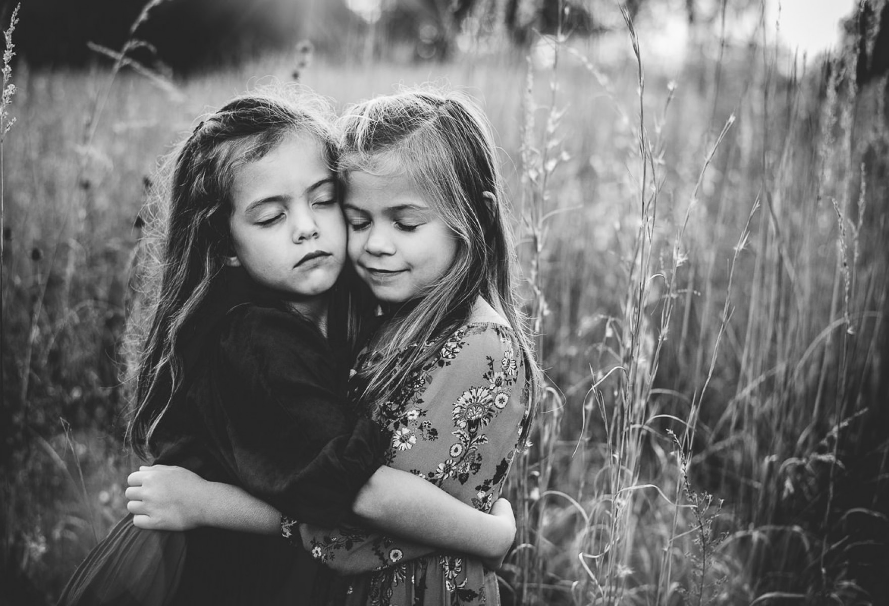 black and white photo of two girls hugging in a field