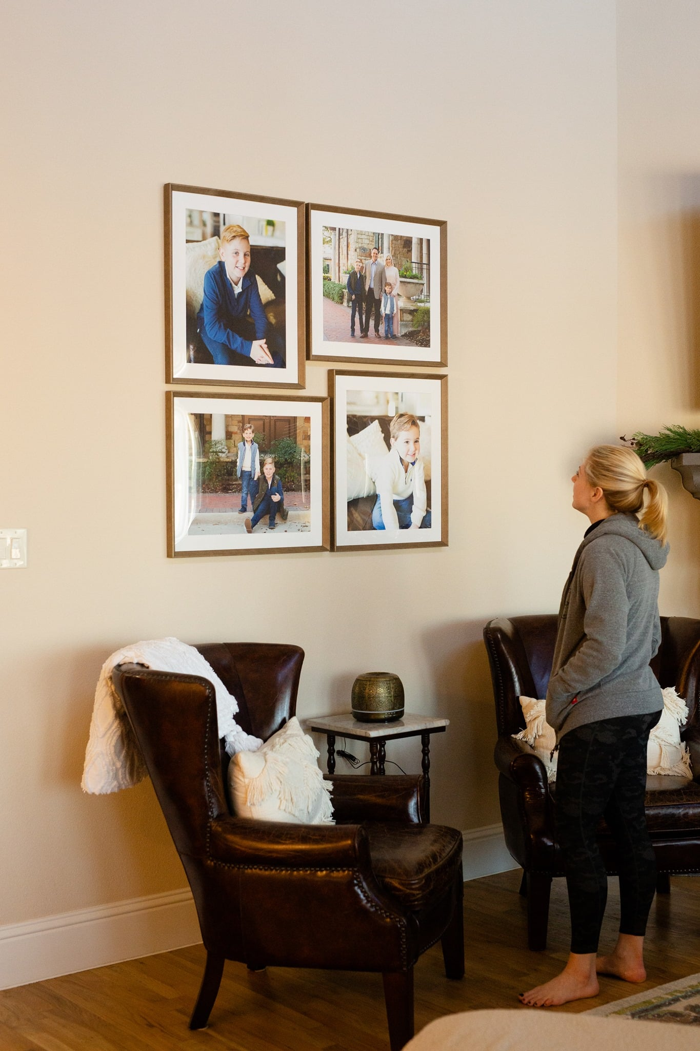 A client admiring her prints on her living room wall