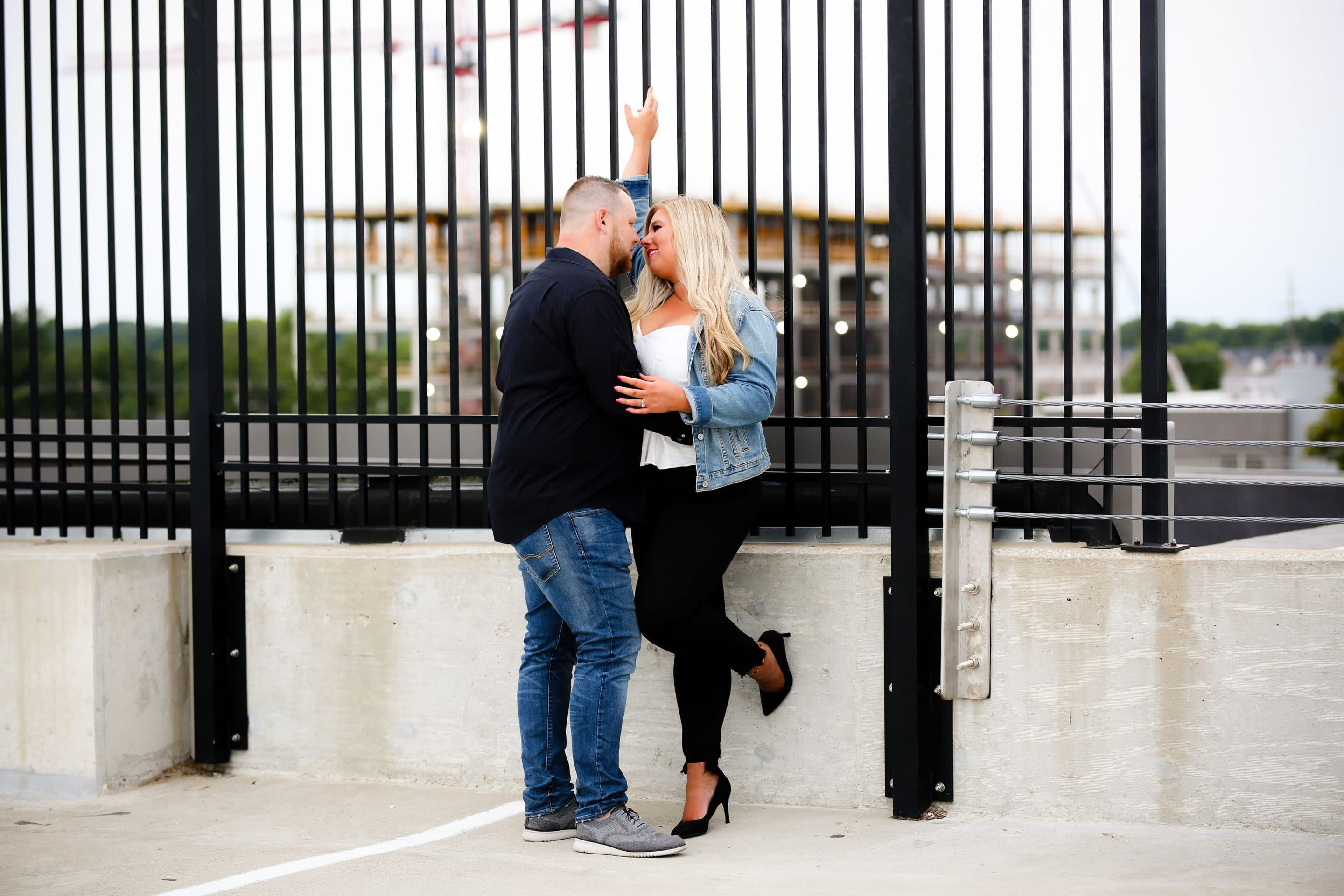 portrait of a couple standing together on top of a parking garage