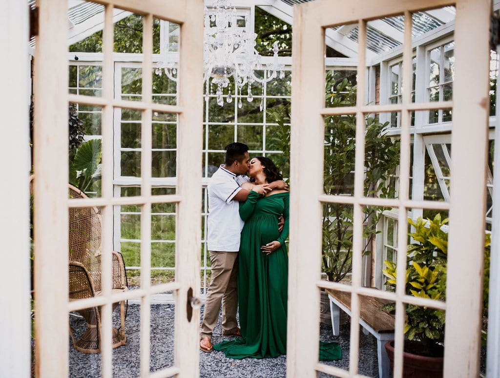 portrait of pregnant woman with her partner inside greenhouse
