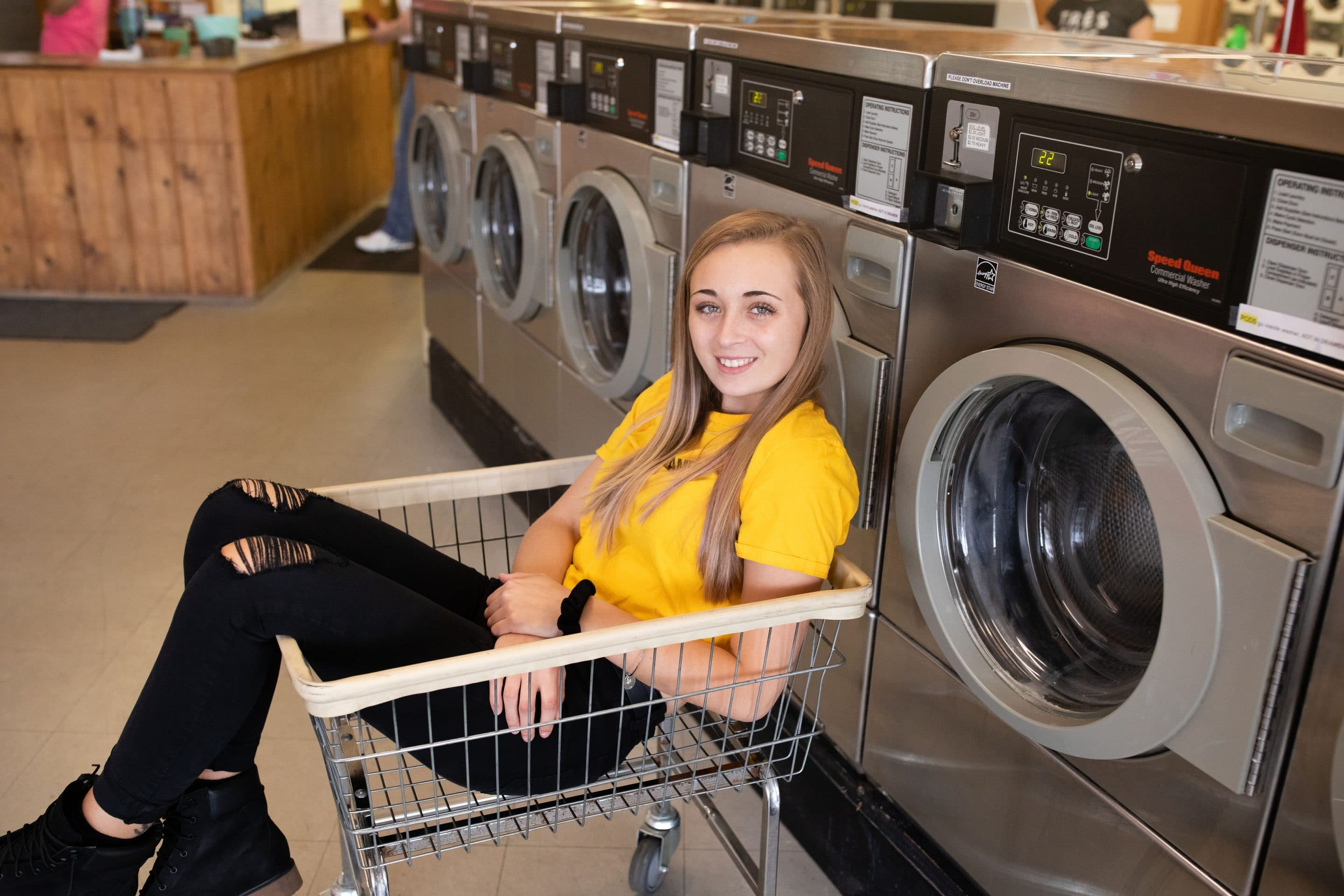 girl sitting in laundry cart inside laundromat