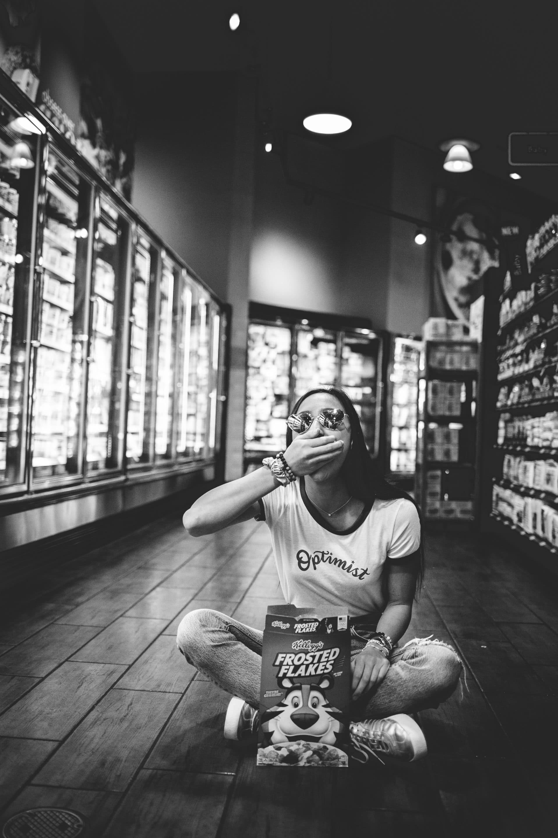 portrait of a girl sitting in a grocery aisle