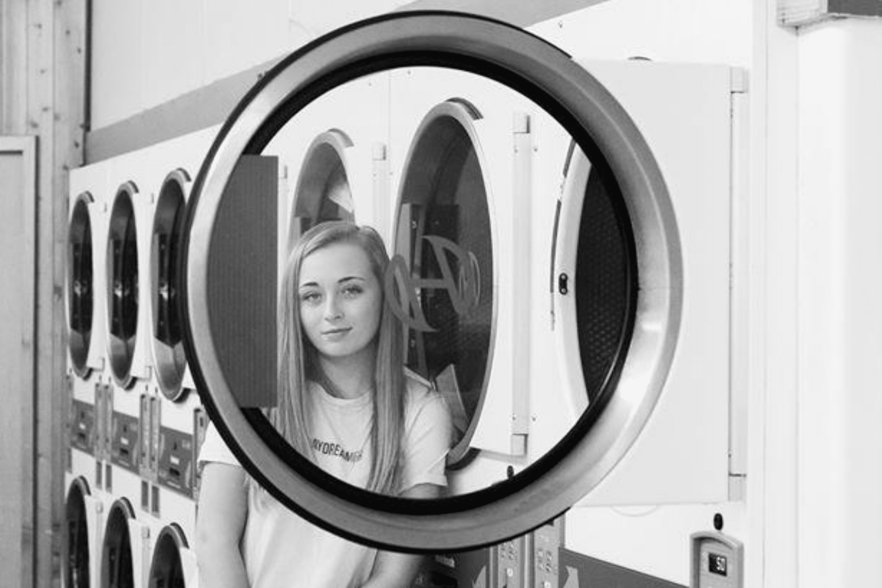 portrait of girl inside a laundromat standing next to dryer